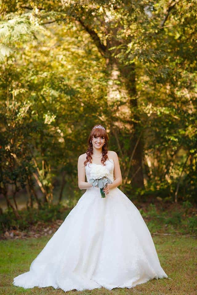 Beautiful Bride outside on a sunny day in a lace wedding gown with bridal bouquet