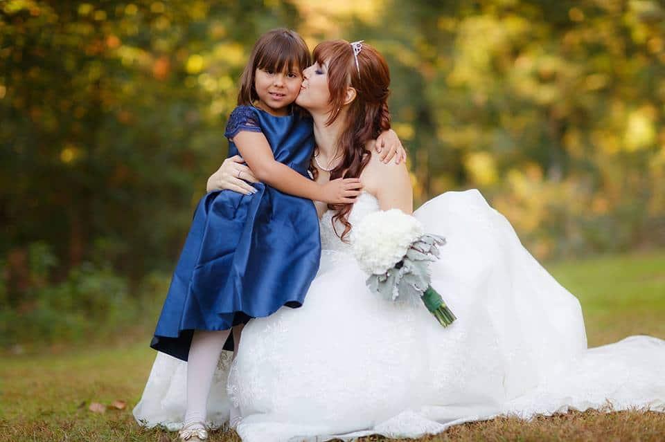 Bride kissing flowergirl in blue flowergirl dress at an outdoor venue in Atlanta