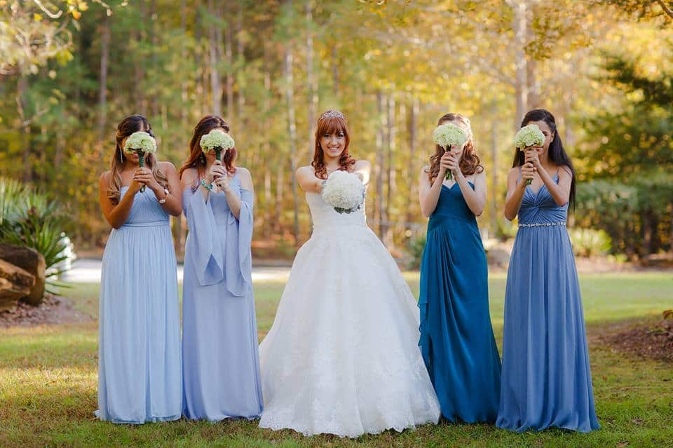 Fun bridal photography with Bridesmaids at outdoor wedding venue not far from Stone Mountain with Bride holding bridal bouquets in front of faces