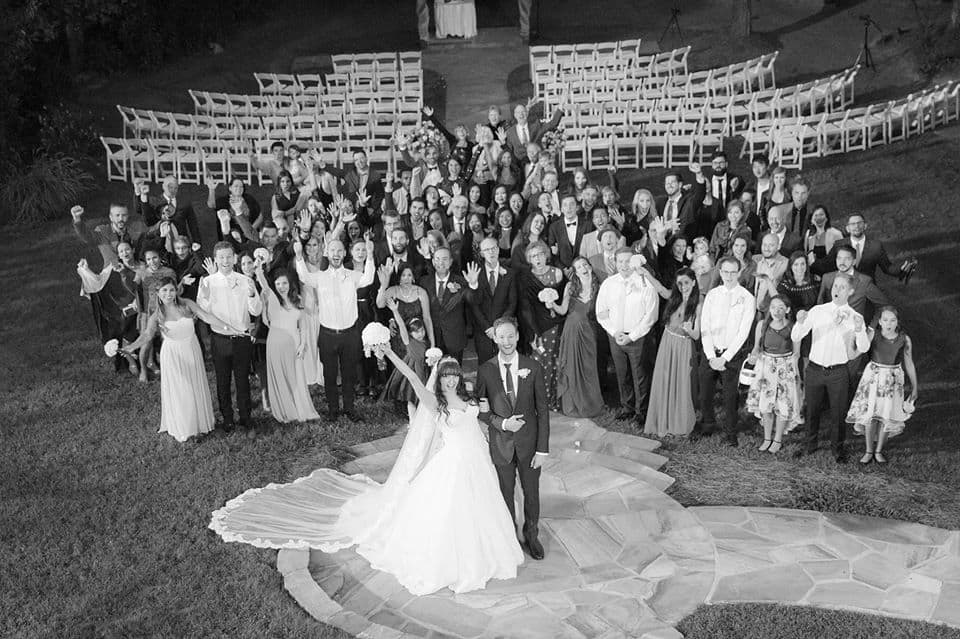 Black and white wedding photography of group shot with bridal party and wedding guests just after wedding ceremony outdoors