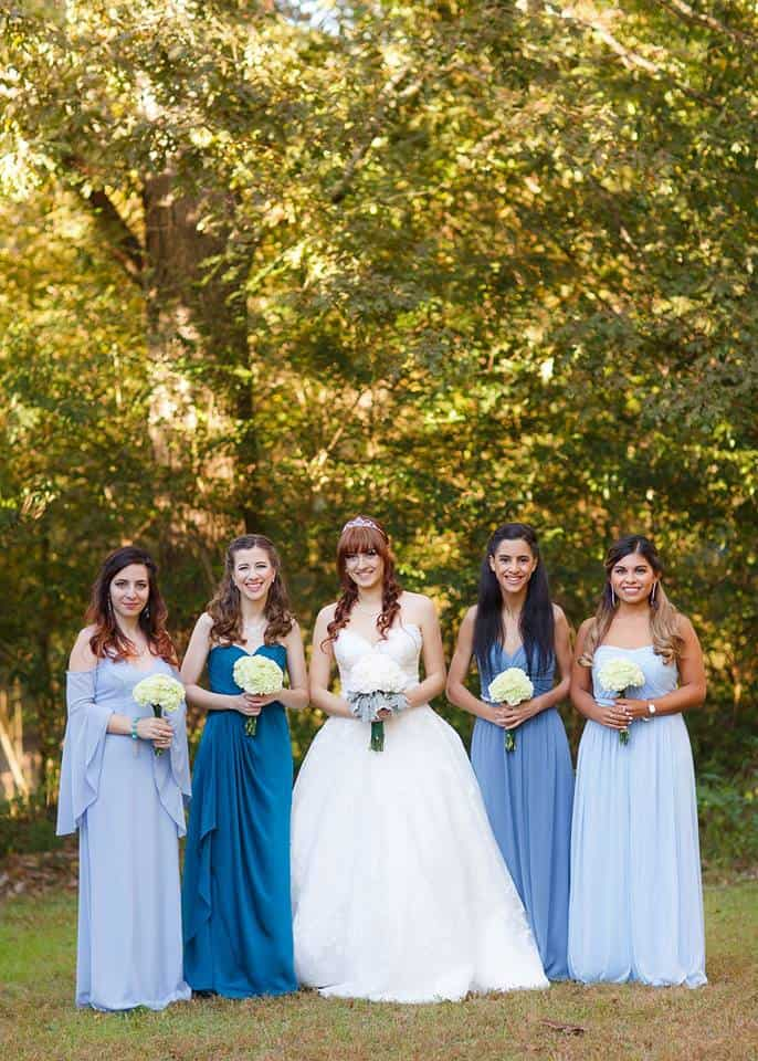 Bride with bridesmaids wearing lavender blue, lilac, teal blue bridesmaids dresses at outdoor wedding venue in Snellville