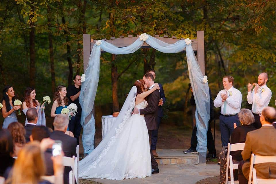 Outdoor wedding ceremony with simple decor at altar on the river with bridal party