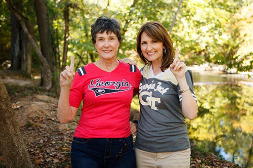 Mother and Daughter Team UGA fan and Ga Tech fan Red and black shirt Grey and Yellow Shirt