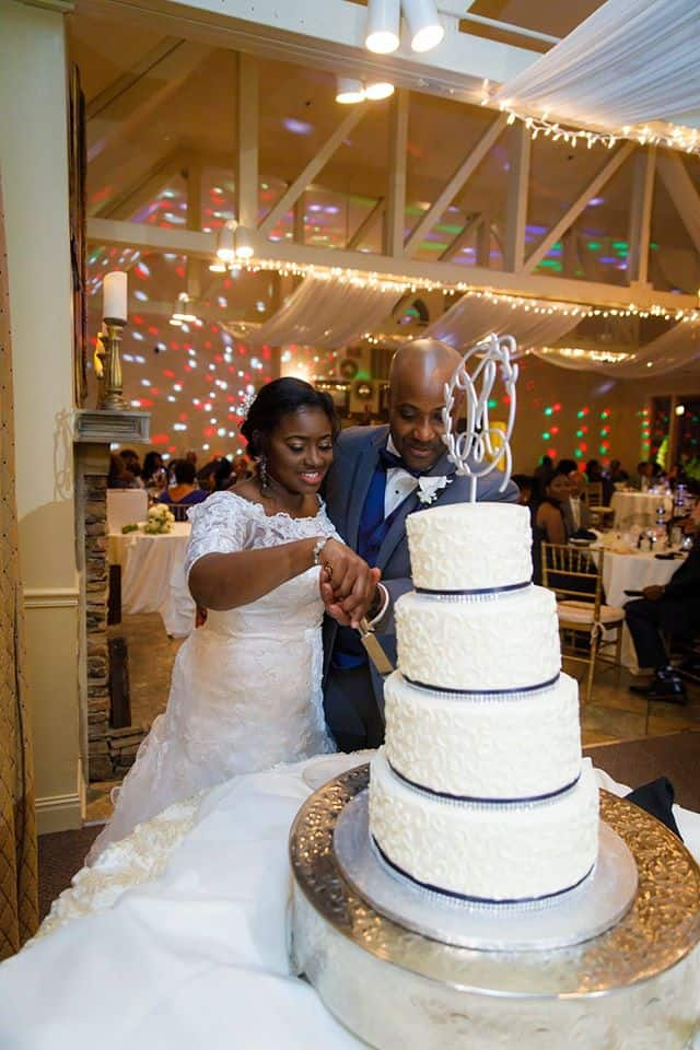 Bride and groom cut into 4 tiered wedding cake