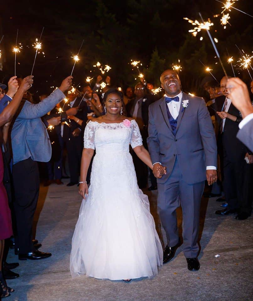 bride and groom smiling as they walk through a sea of sparklers lighting up the sky
