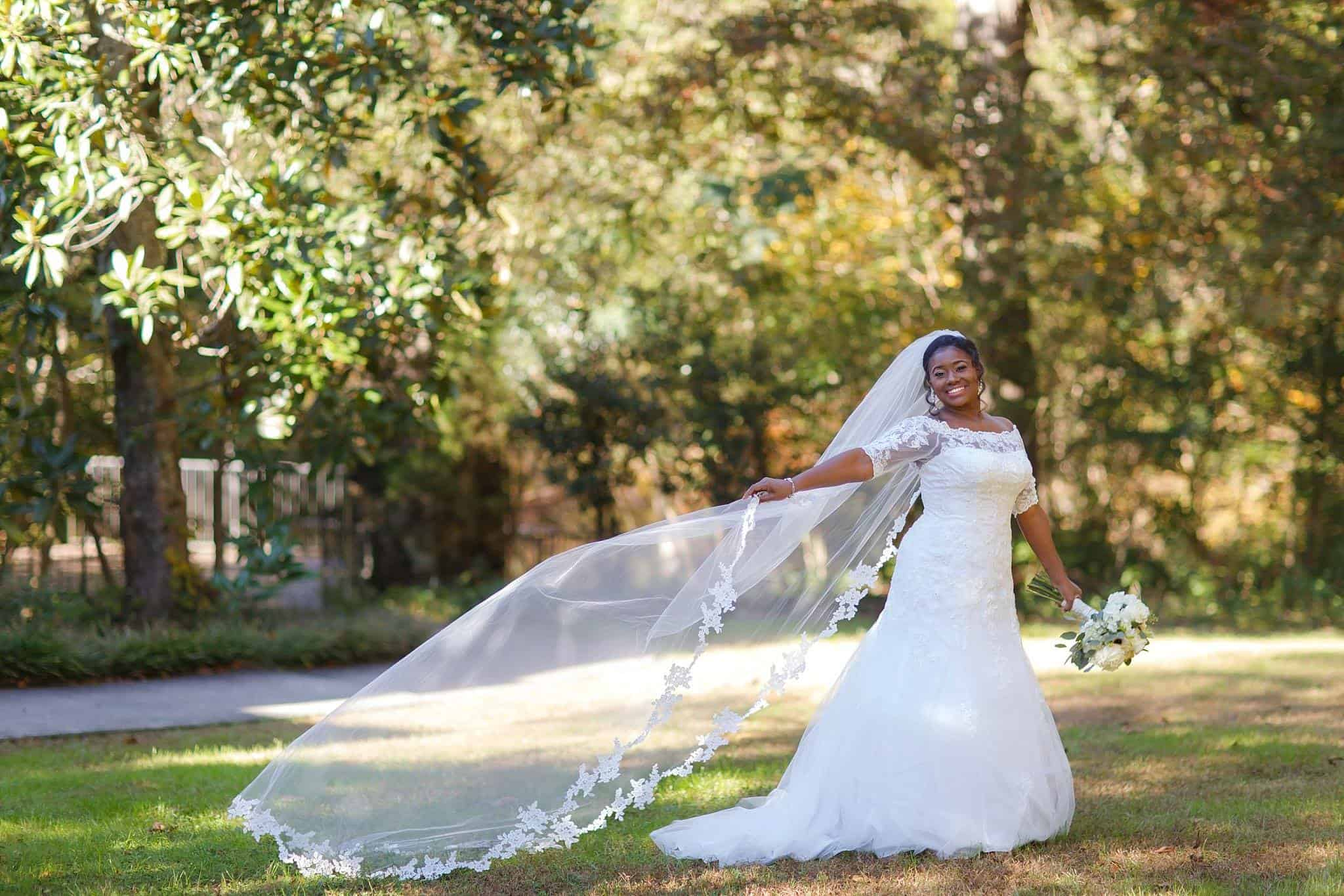 Bride posing on lawn with long flowing veil