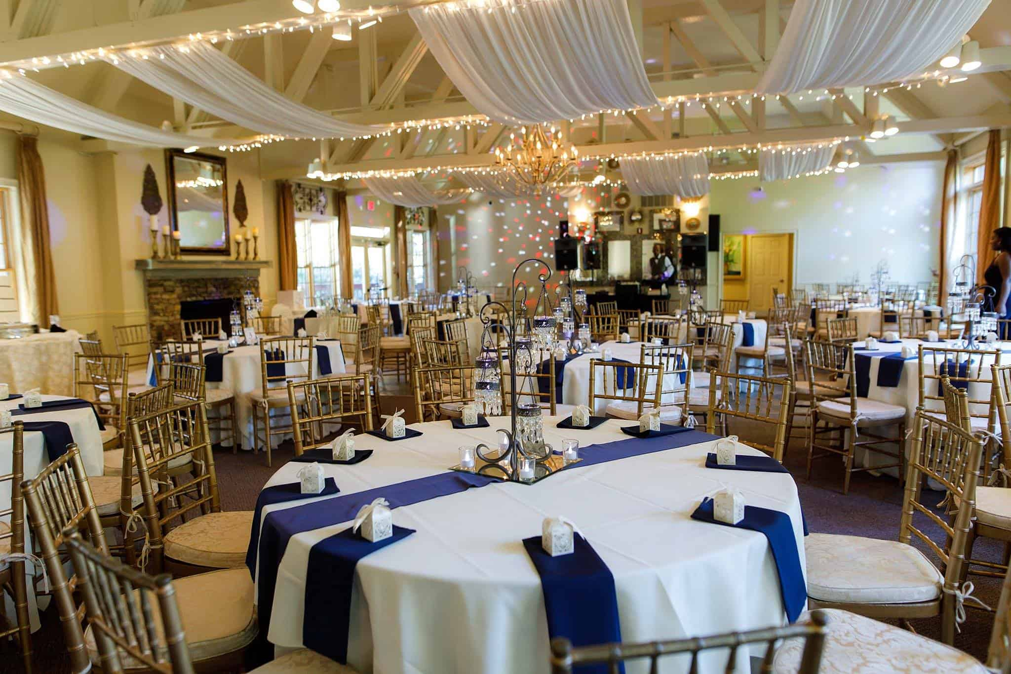 Reception hall with ivory tablecloths and navy blue folded napkins
