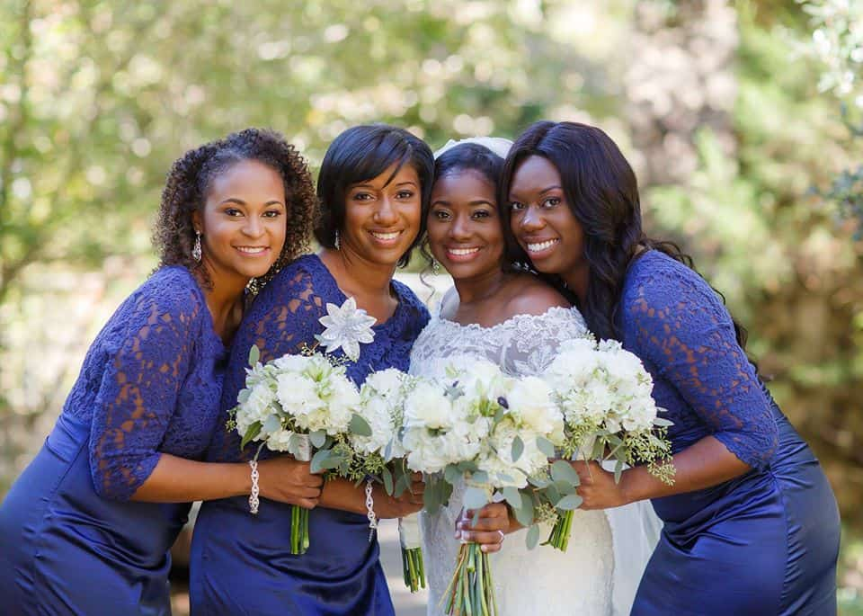 Bride posing with three bridesmaids in navy blue dresses