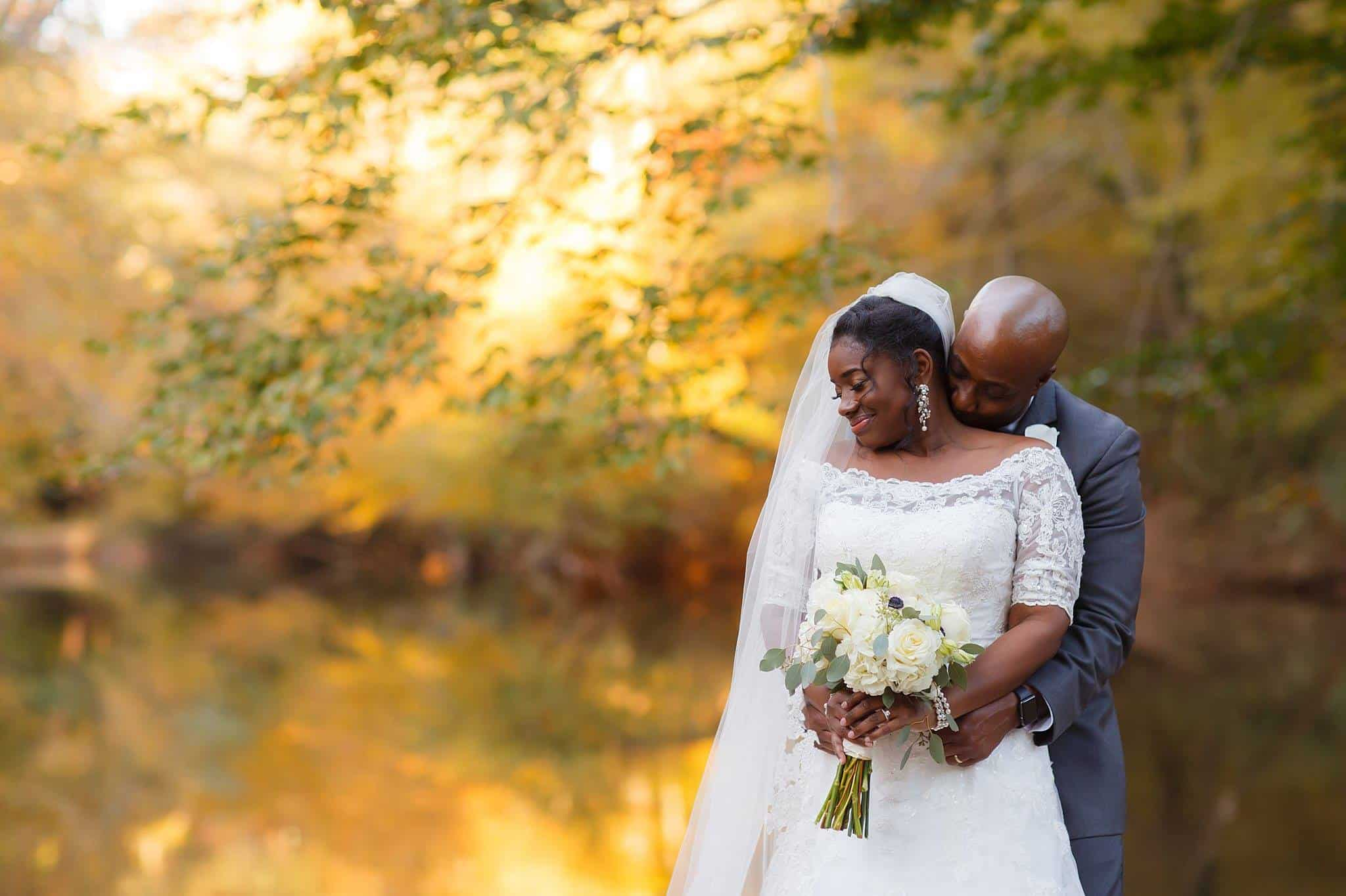 bride and groom embracing for wedding photo surrounded by fall leaves