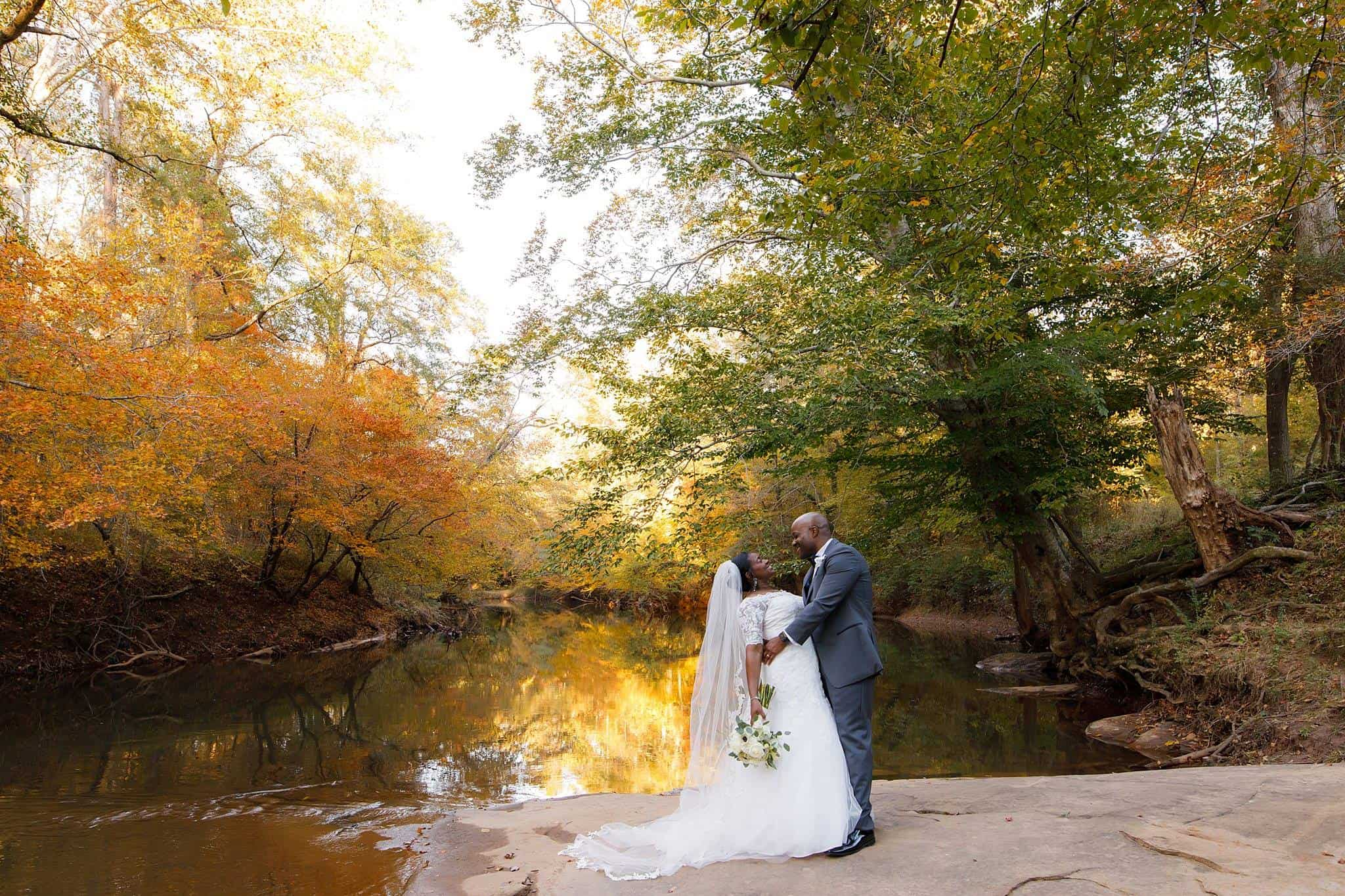 Groom dips his bride in an elegant photo on a rivers edge