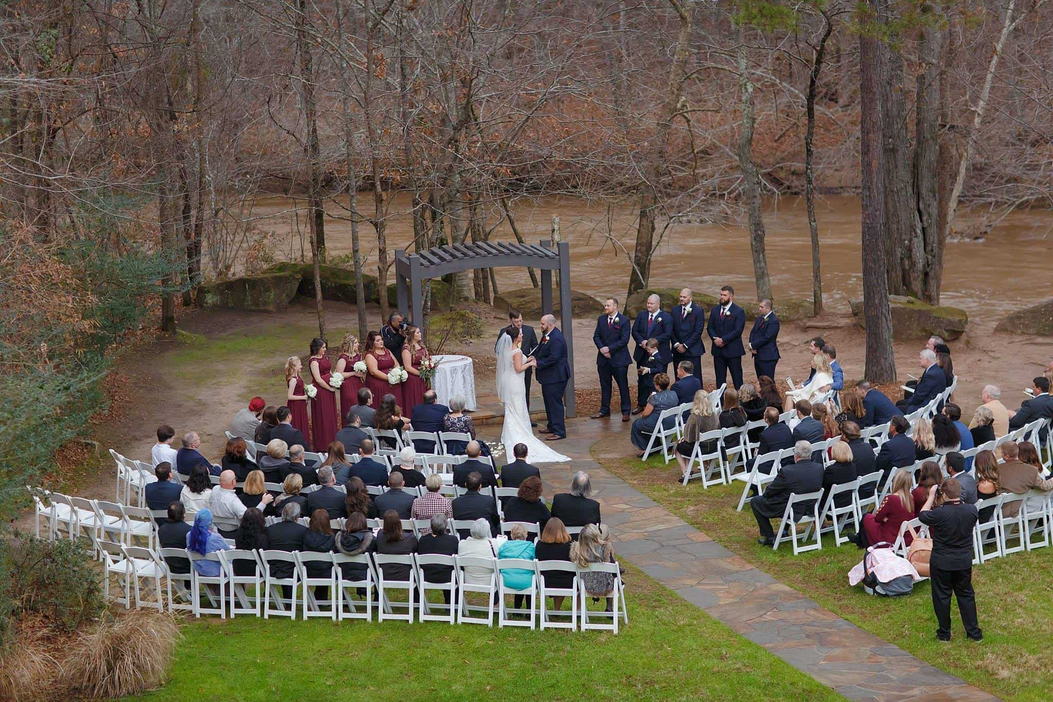 December Winter Outdoor Wedding Ceremony on a river in Snellville with bridal party, bride and groom at the altar with guests seated