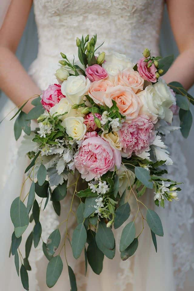 Bride holding Cascading Bridal Bouquet with pink roses, pink peonies, cream roses, eucalyptus