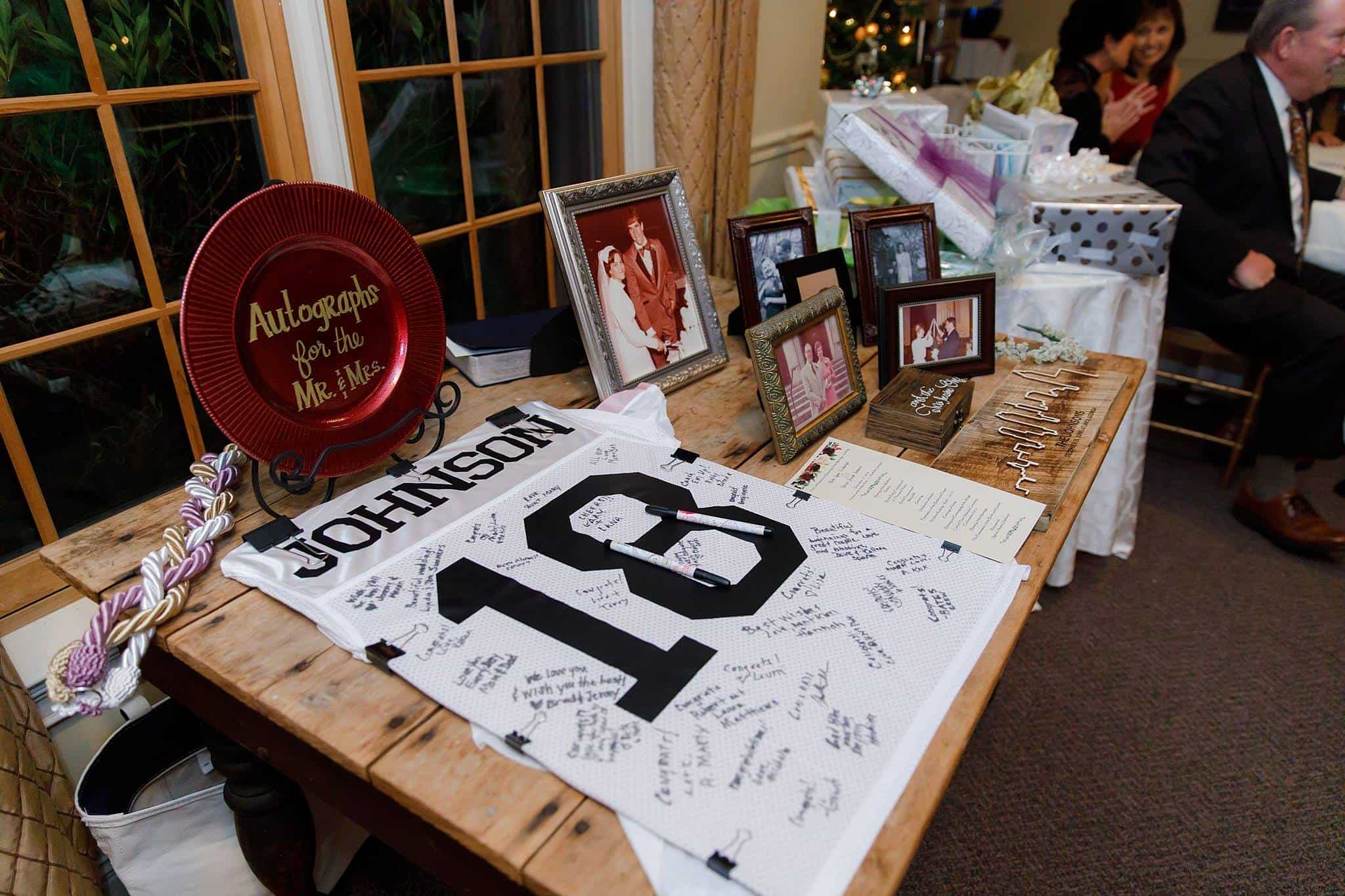 Football Jersey displayed on table for guests to sign next to photos of family