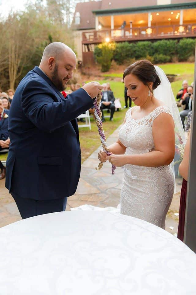 Bride and Groom at the altar doing a wedding ritual called the the Cord of Three Strands with gold, purple and white strands depicting God, the groom and the bride