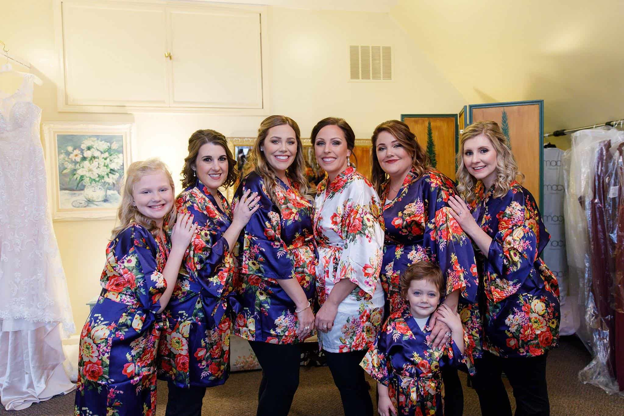 Bride with Bridesmaids wearing bright blue and pink robes before dressing in bridal suite
