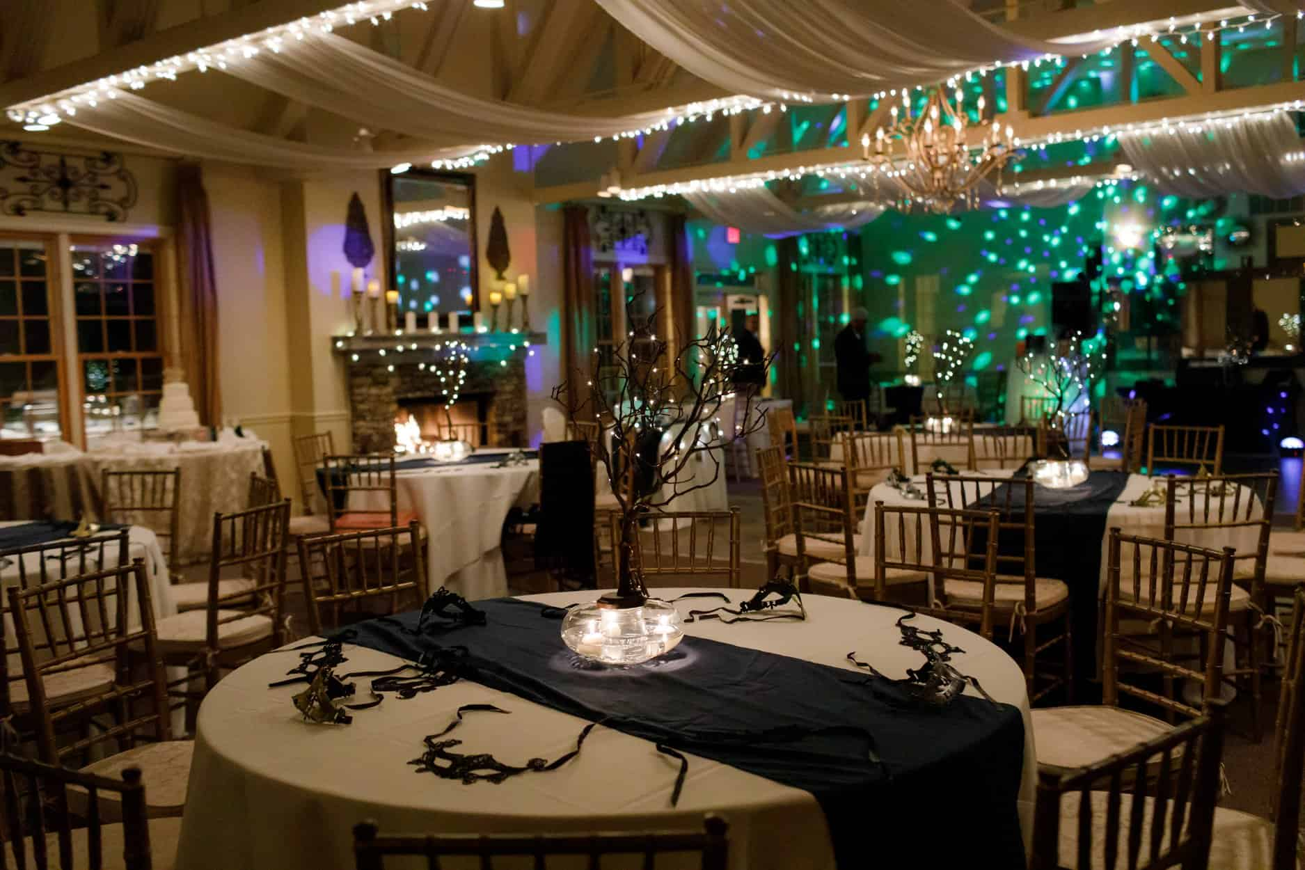 Wedding Reception Decor with Black Masks at Tables with tall branch centerpieces with lights and teal blue lighting on walls for dancing