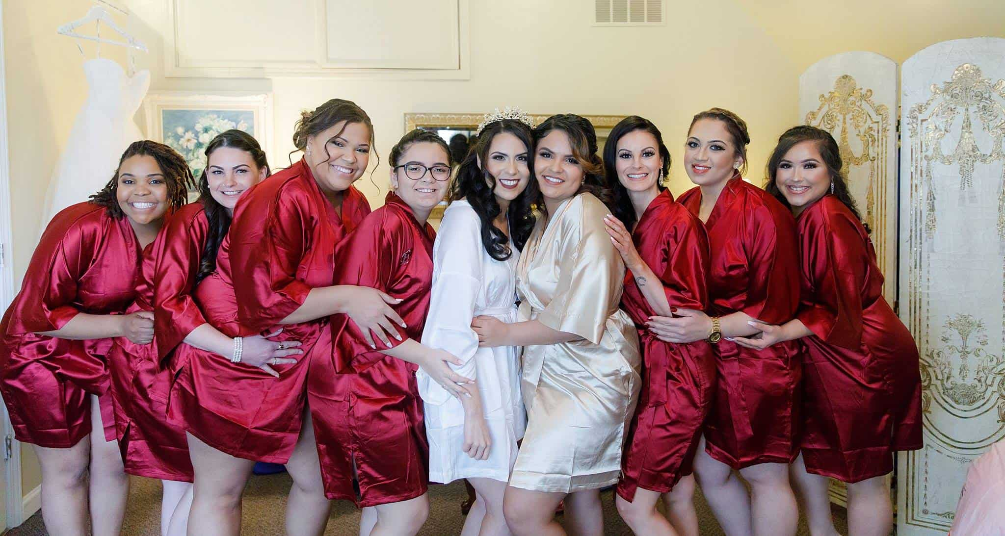 Bride with Bridesmaids wearing red satin robes in bride's dressing room