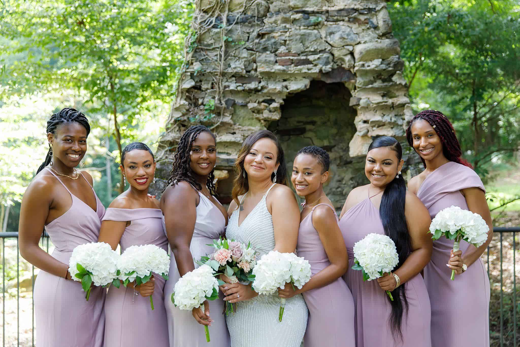 Beautiful bridesmaids in full-length lilac gowns