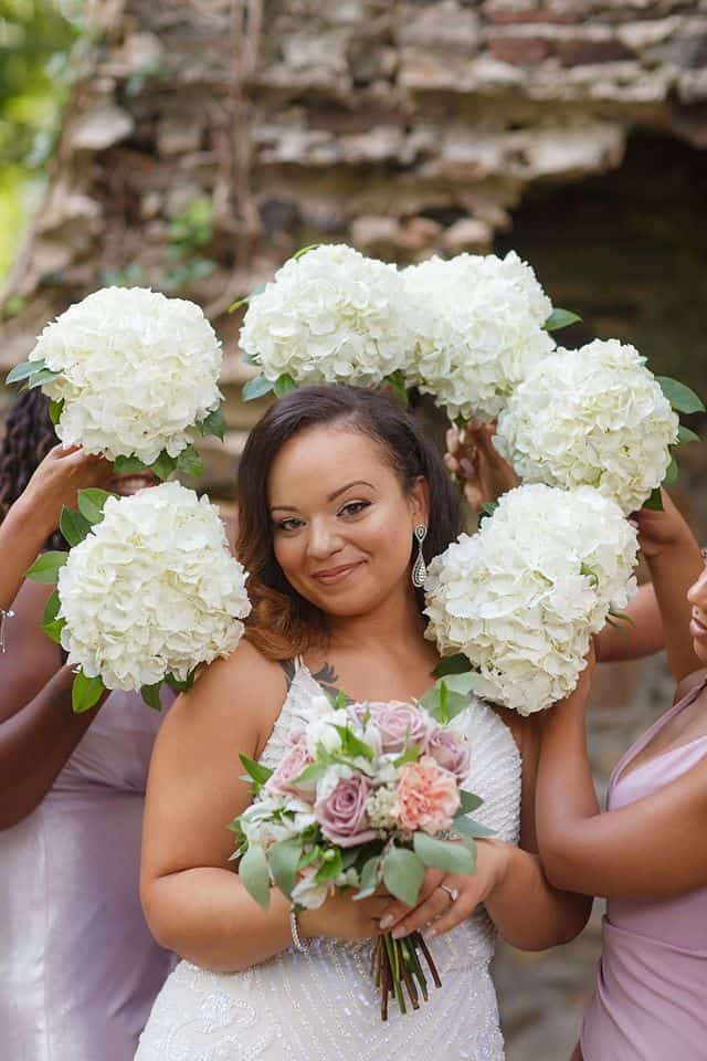 Beautiful bride posing with bridesmaids bouquets surrounding her