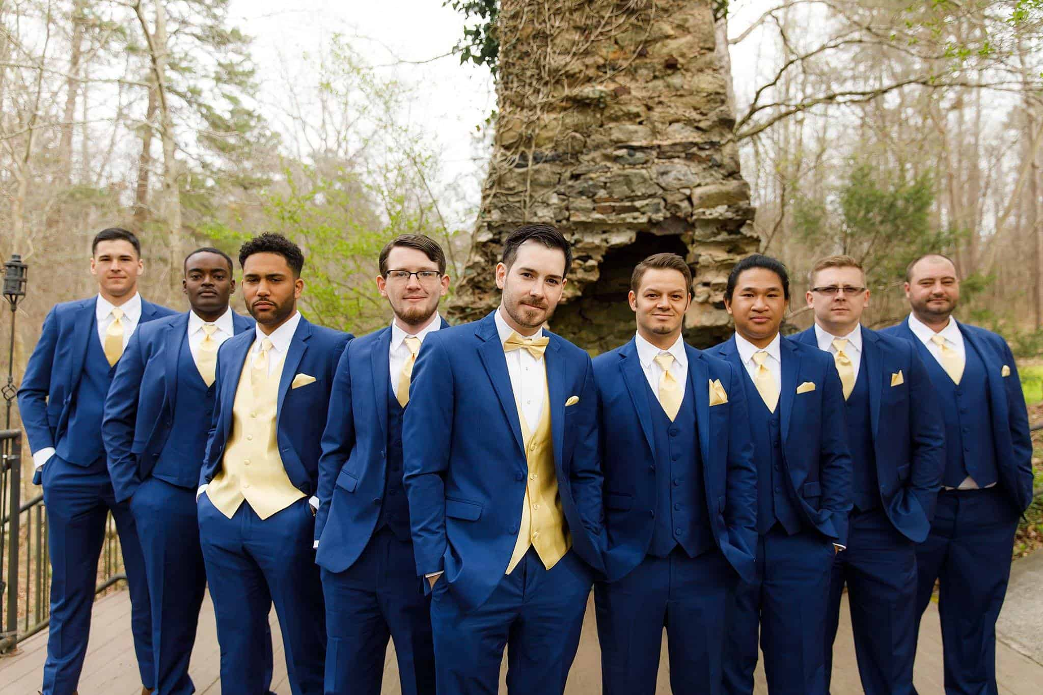 Groom in Navy Suit, Gold Vest and Bowtie with Groomsmen in Navy Suits, Navy Vest, Gold Tie and Pocket Square outdoors in front of chimney