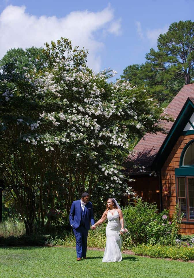 Bride and groom stroll through the front lawn under the grand crepe myrtle trees