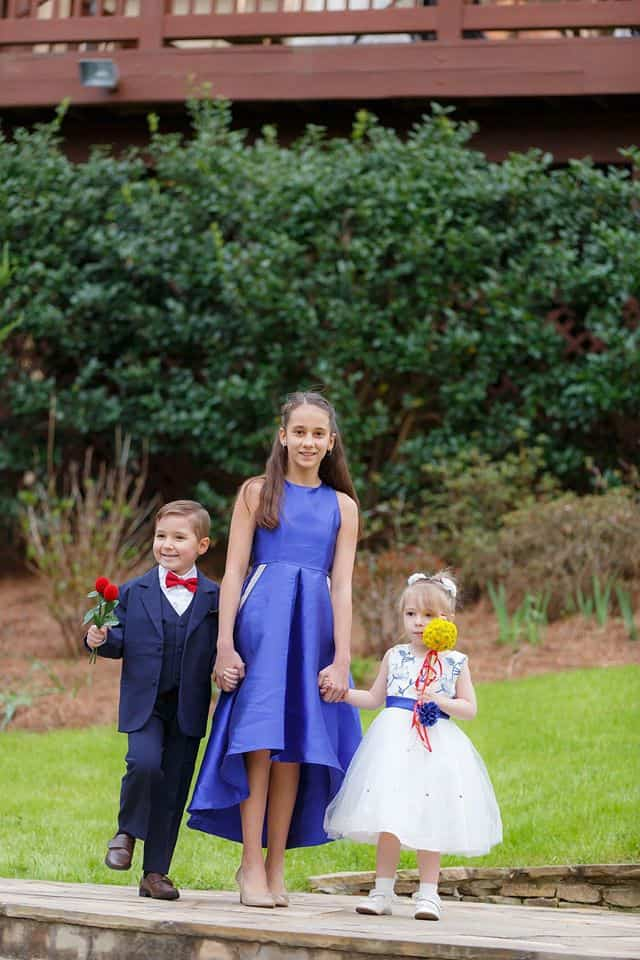 Junior Bridesmaid holding hands with a ringbearer who is holding 2 red roses for Beauty and the Beast theme and flowergirl
