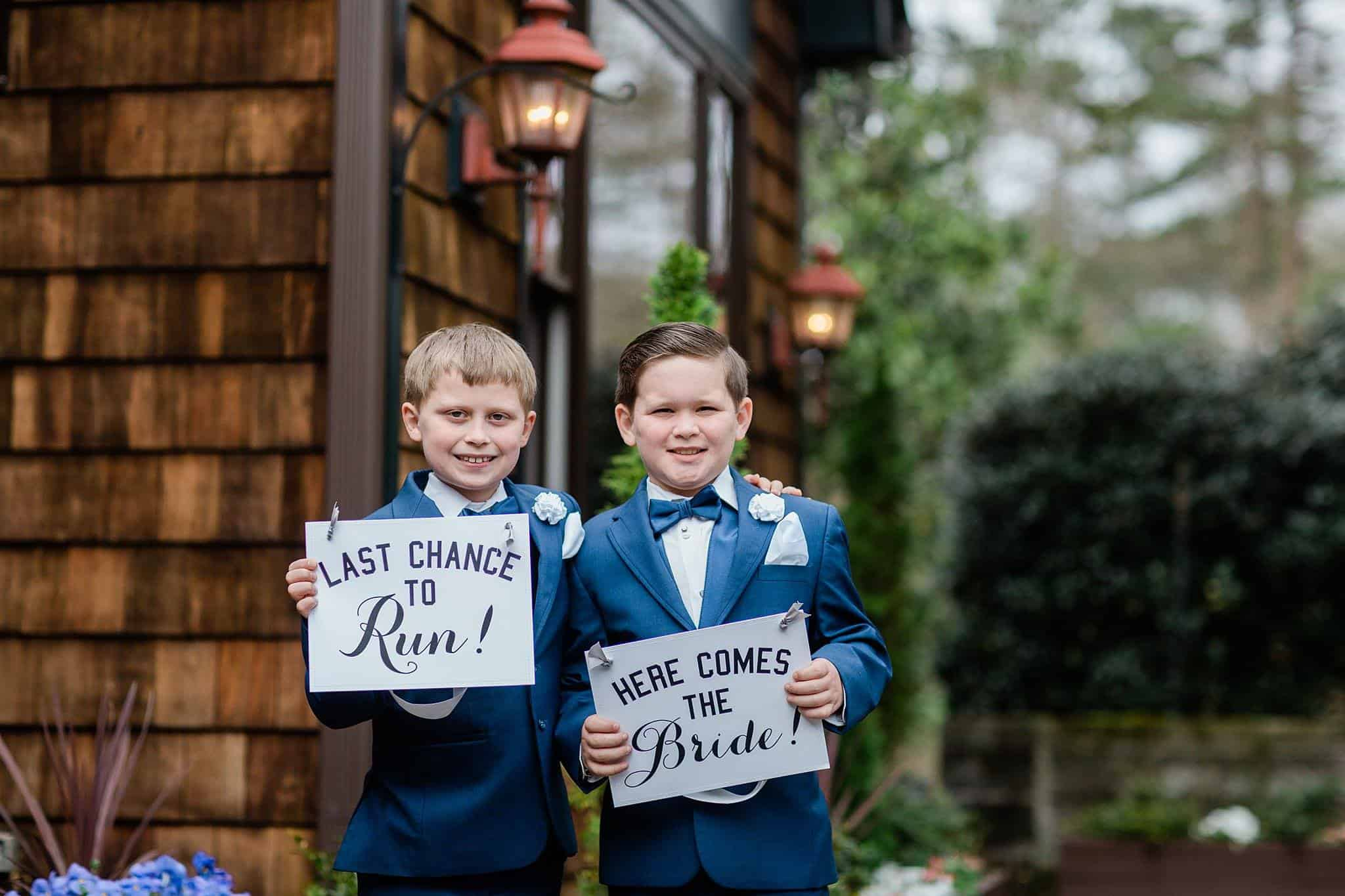 "Two Ring bearers holding signs that say ""Here comes the bride"" and ""Last Chance to Run"" in blue tuxedos with blue bow ties and white pocket squares outside wedding venue located not far from Loganville"