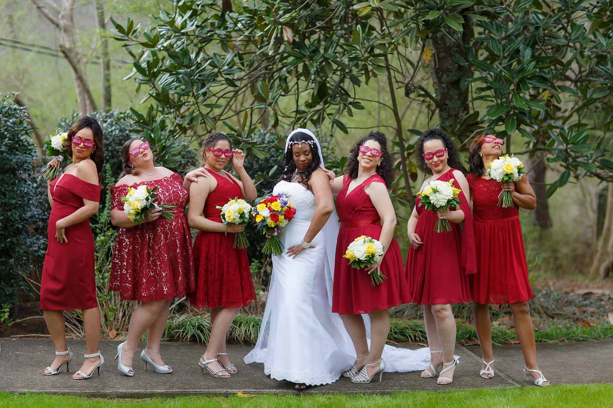 Bridesmaids with Bride having fun posing with red sunglasses that match red bridesmaids dresses