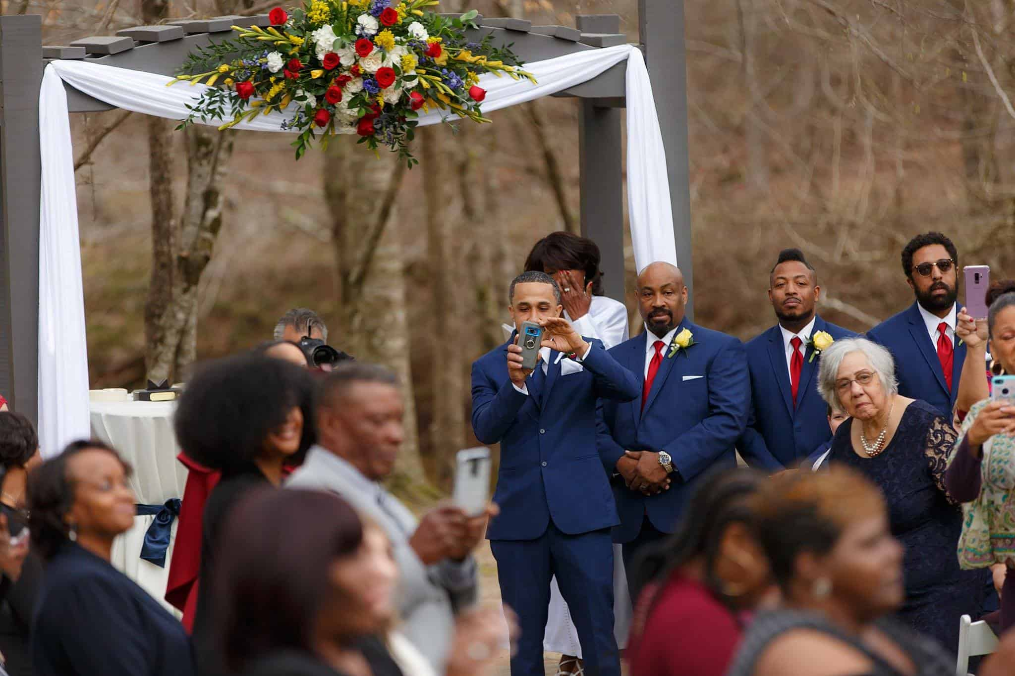 Groom at Altar takes photo of Bride Walking Down the Aisle in Outdoor Wedding Ceremony