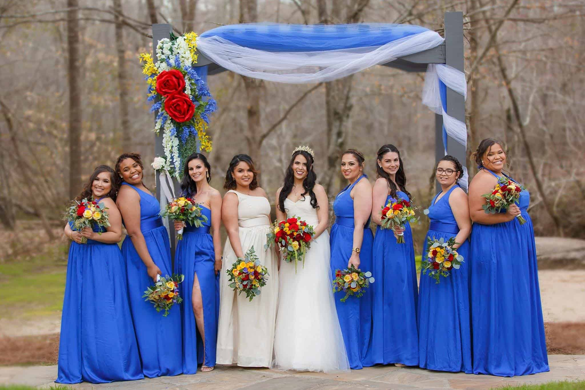 Bride with Bridesmaids in long blue dresses at the arbor draped in blue and white tulle with large floral display while holding yellow, red bouquets