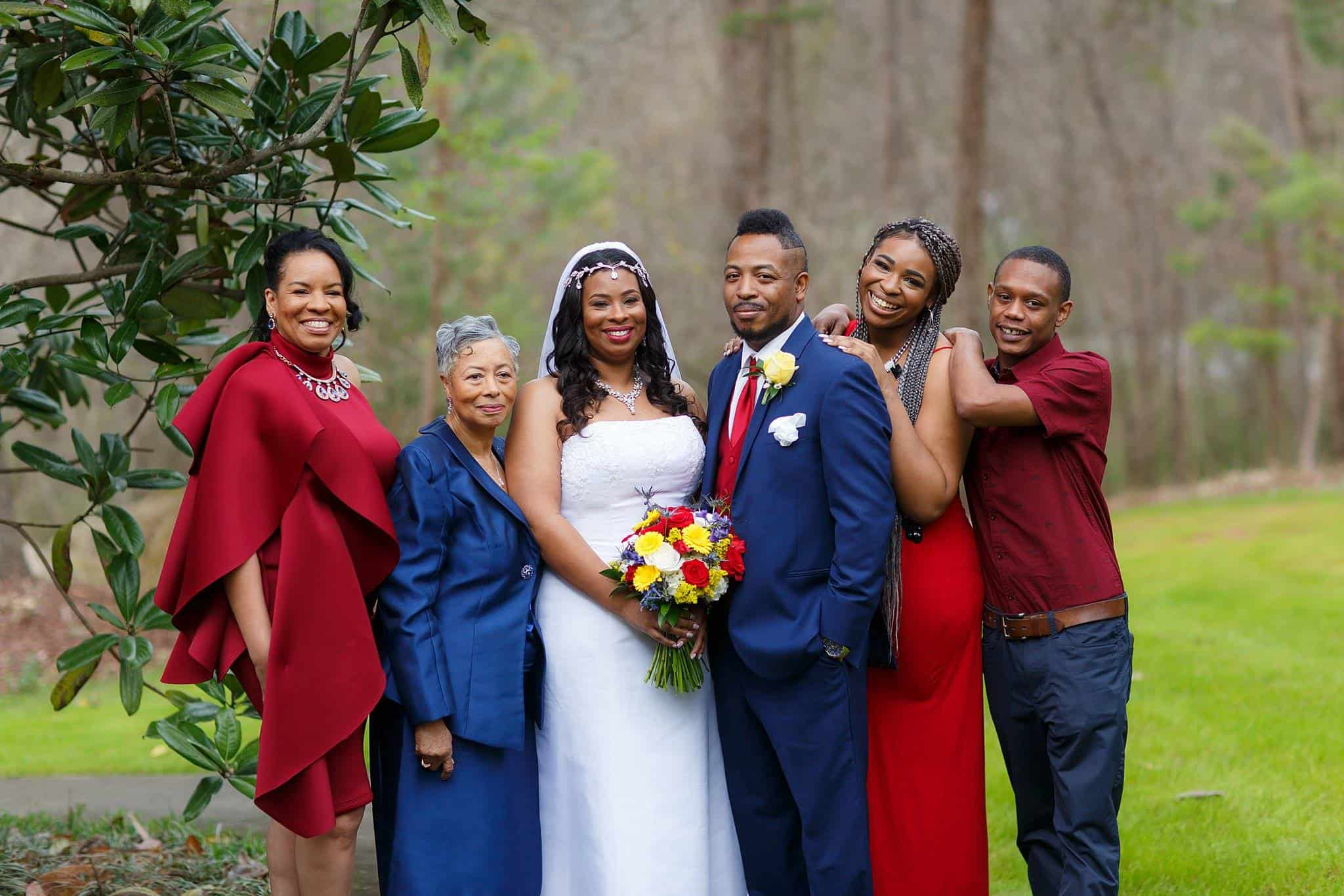 Bride with family posing outdoors with mother, maid of honor, brother, sister and son