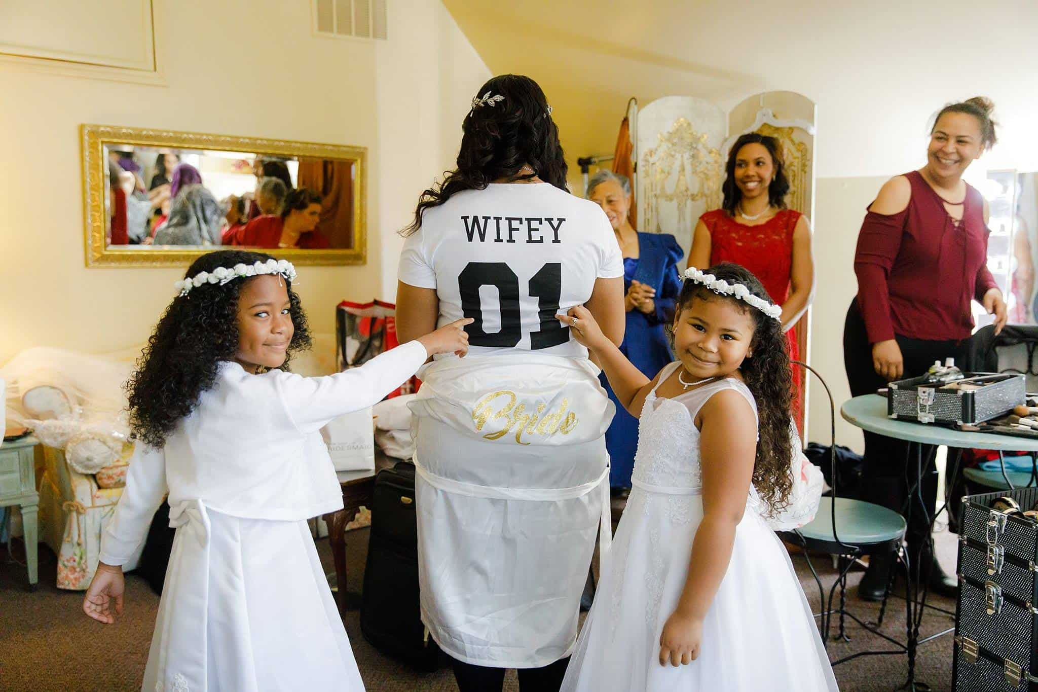 Bride in Bridal Suite with flowergirls pointing at her teeshirt