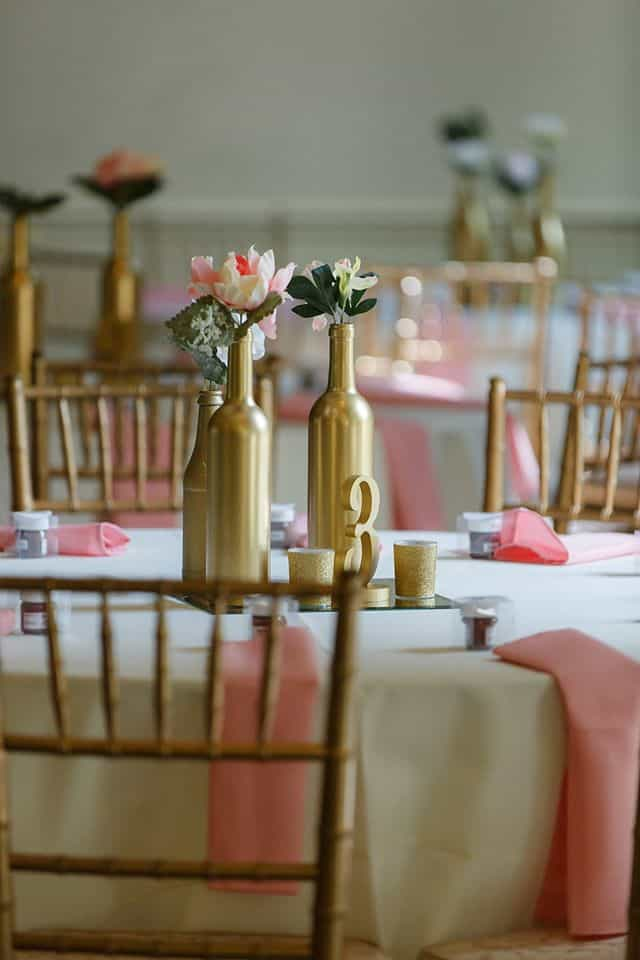 Blush pink napkins on guest table with blush pink silk flowers in gold vases