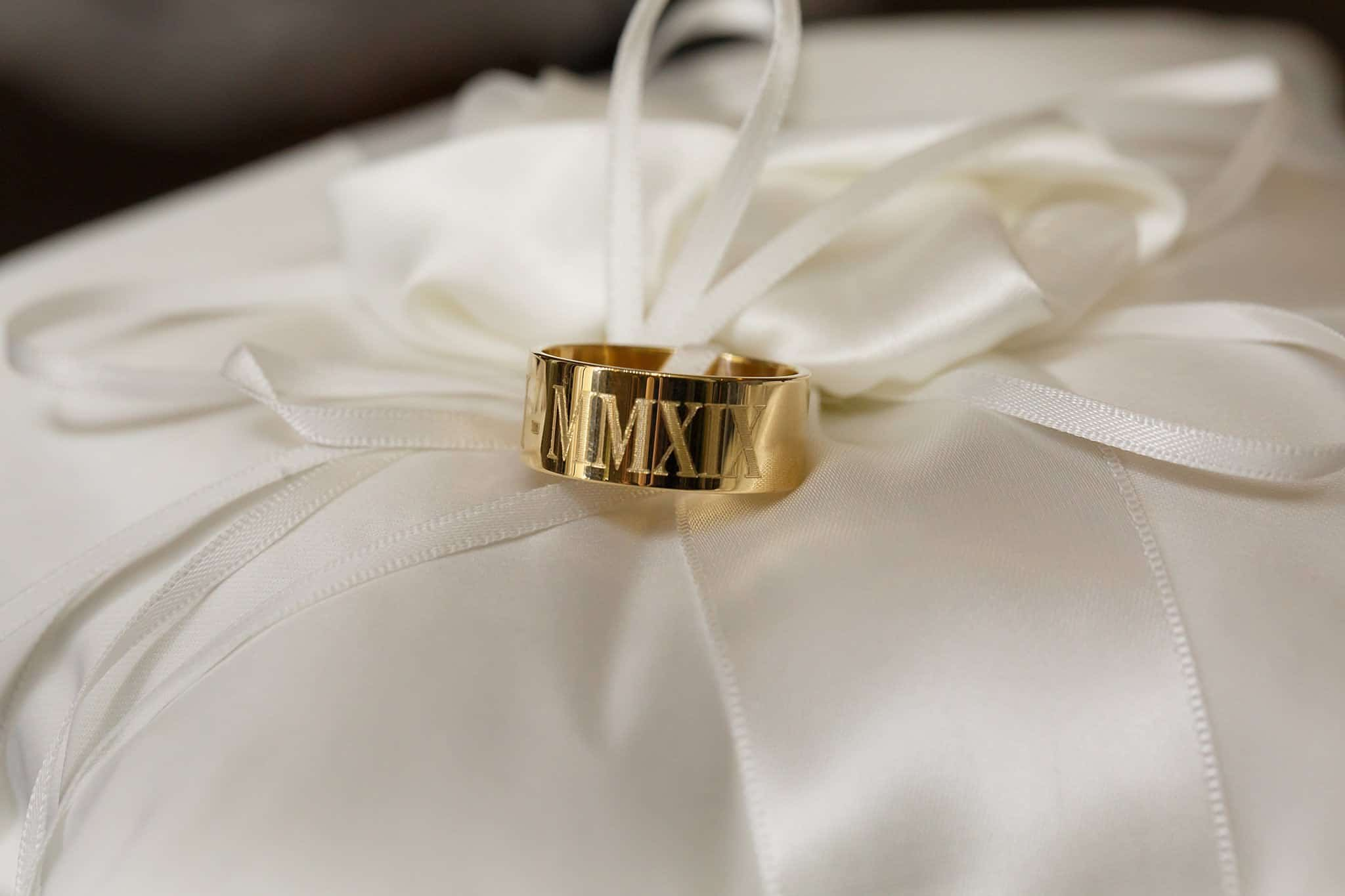 Gold Grooms ring on satin white ring bearer pillow inscribed with Roman Numerals for 2019