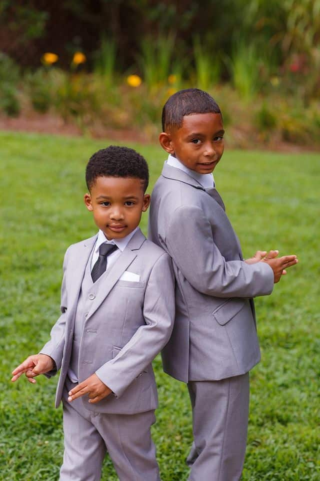 Young boys in a wedding wearing grey suits posing outdoors at a wedding venue near Snellville