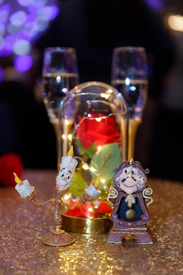 Beauty and the Beast Wedding Theme with Disney characters on guest tables at wedding reception and red rose encased in glass