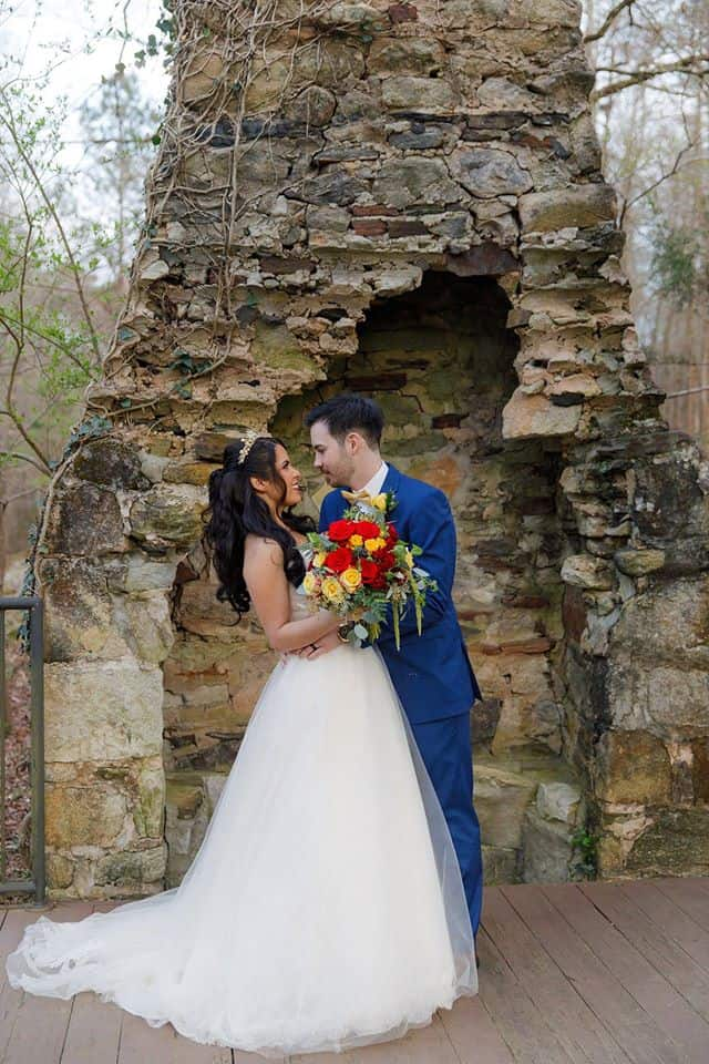 Bride holding a bouquet of red and gold flowers with Groom posing outdoors in front of chimney