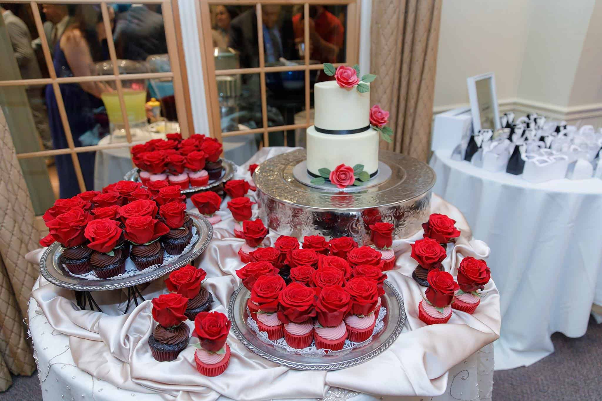Beauty and the Beast Themed Dessert Table at Wedding with Chocolate and Strawberry Cupcakes topped with a Red Rose displayed on silver platters