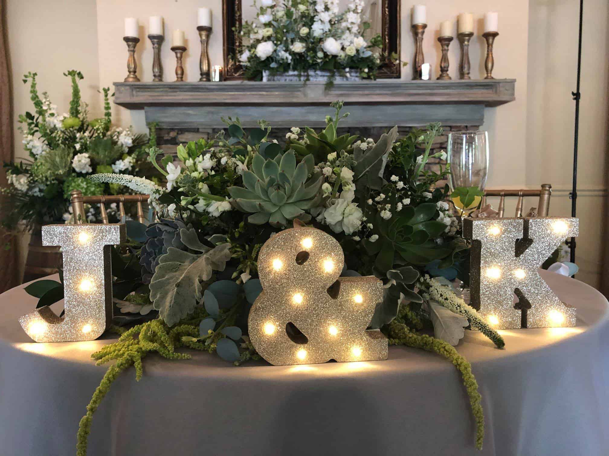 Sweetheart table with large floral arrangement in green and white with large initals of bride and groom lit up