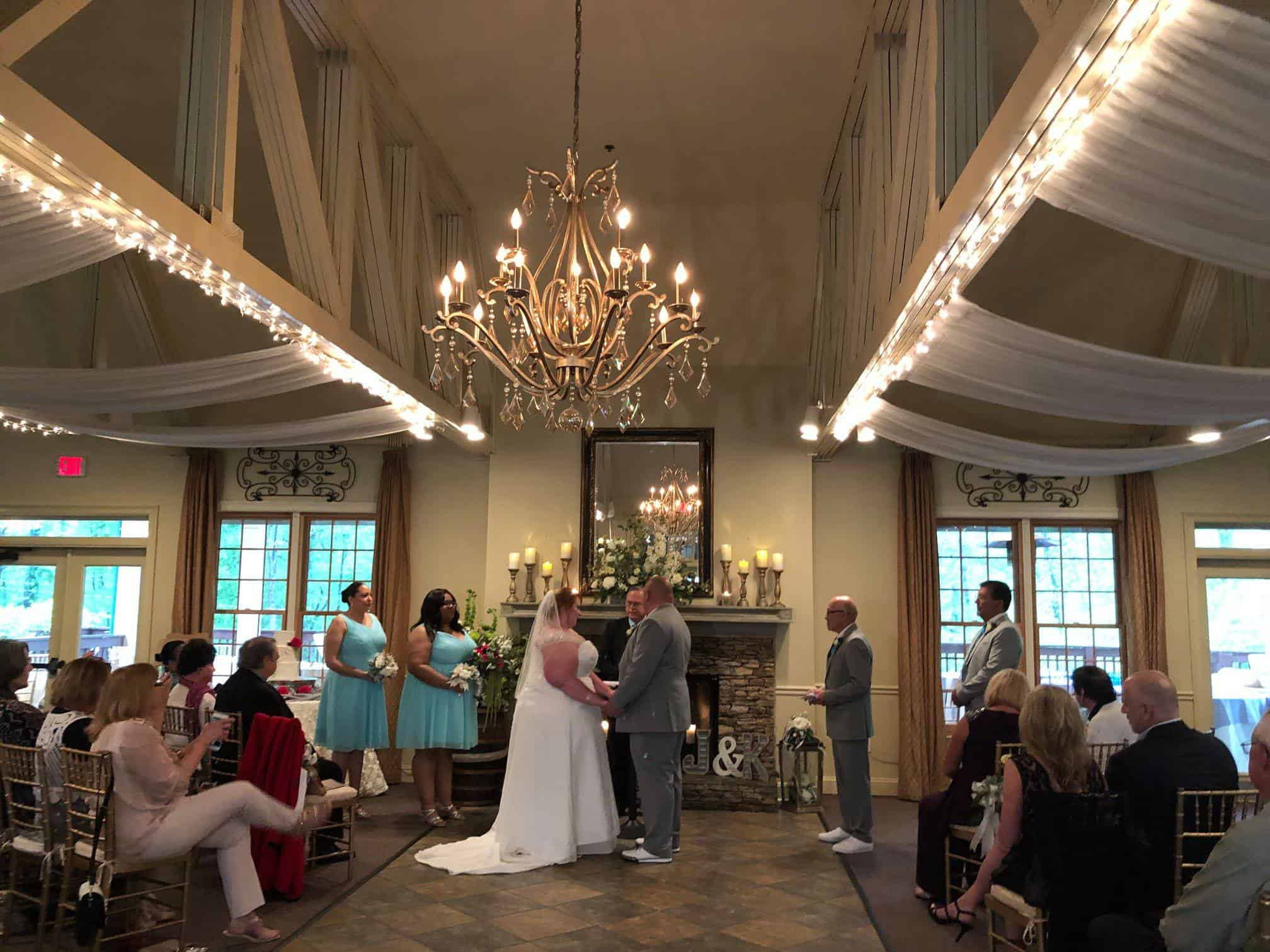 Bride and Groom at Indoor Wedding Ceremony Holding Hands at Ceremony Altar with Bridesmaids in Blue Bridesmaids Dresses and Officiant and Groomsmen