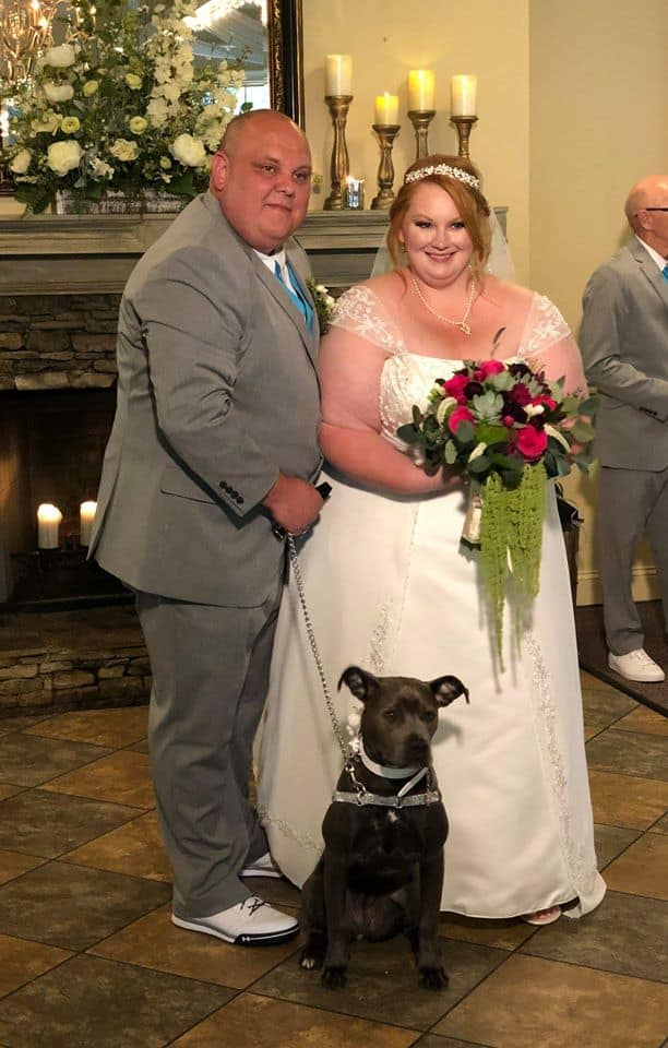 Bride and Groom in front of candlelit fireplace with pet dog