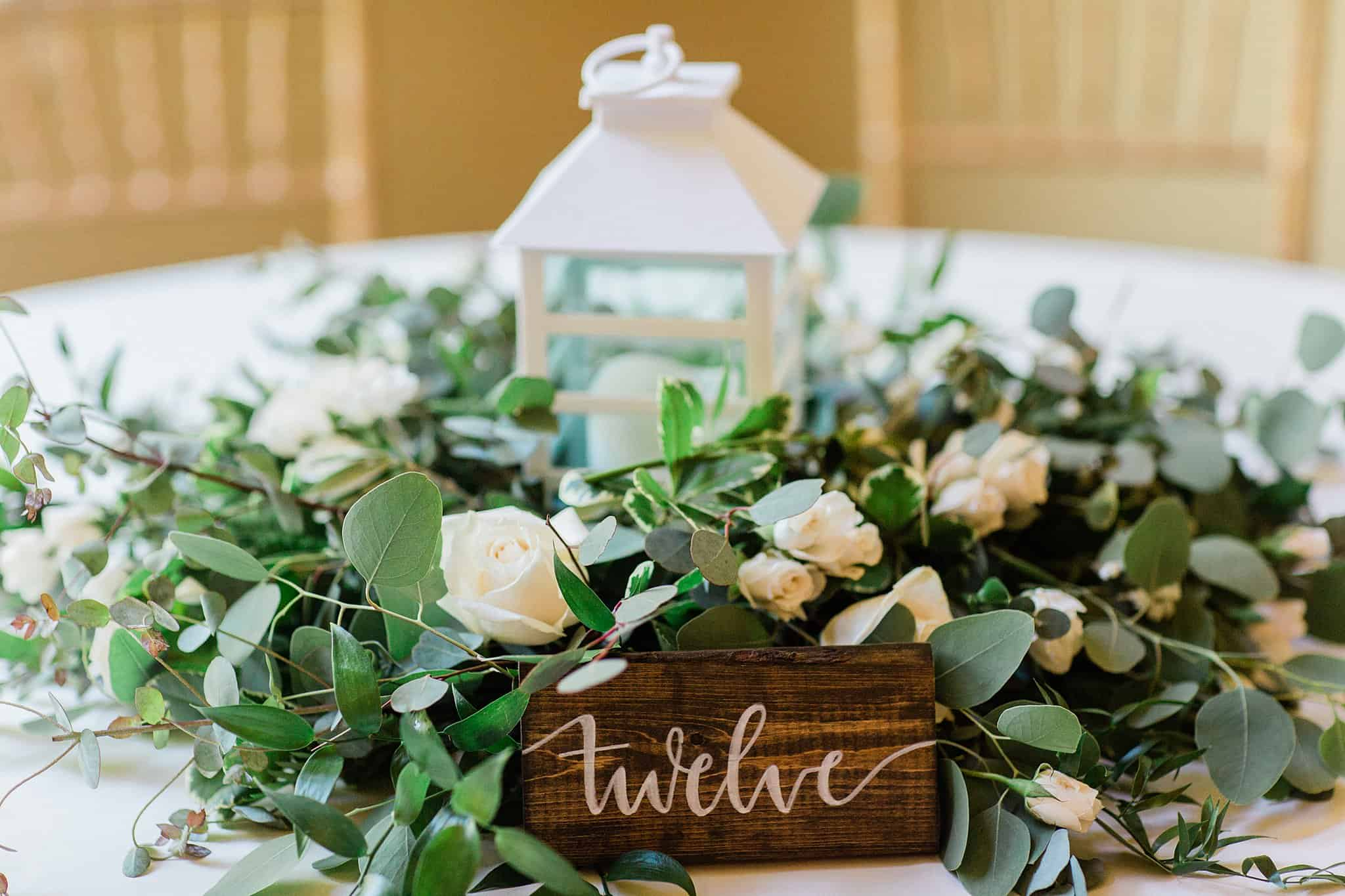 Centerpiece on guest table at wedding with white lantern, eucalyptus, white roses and table sign
