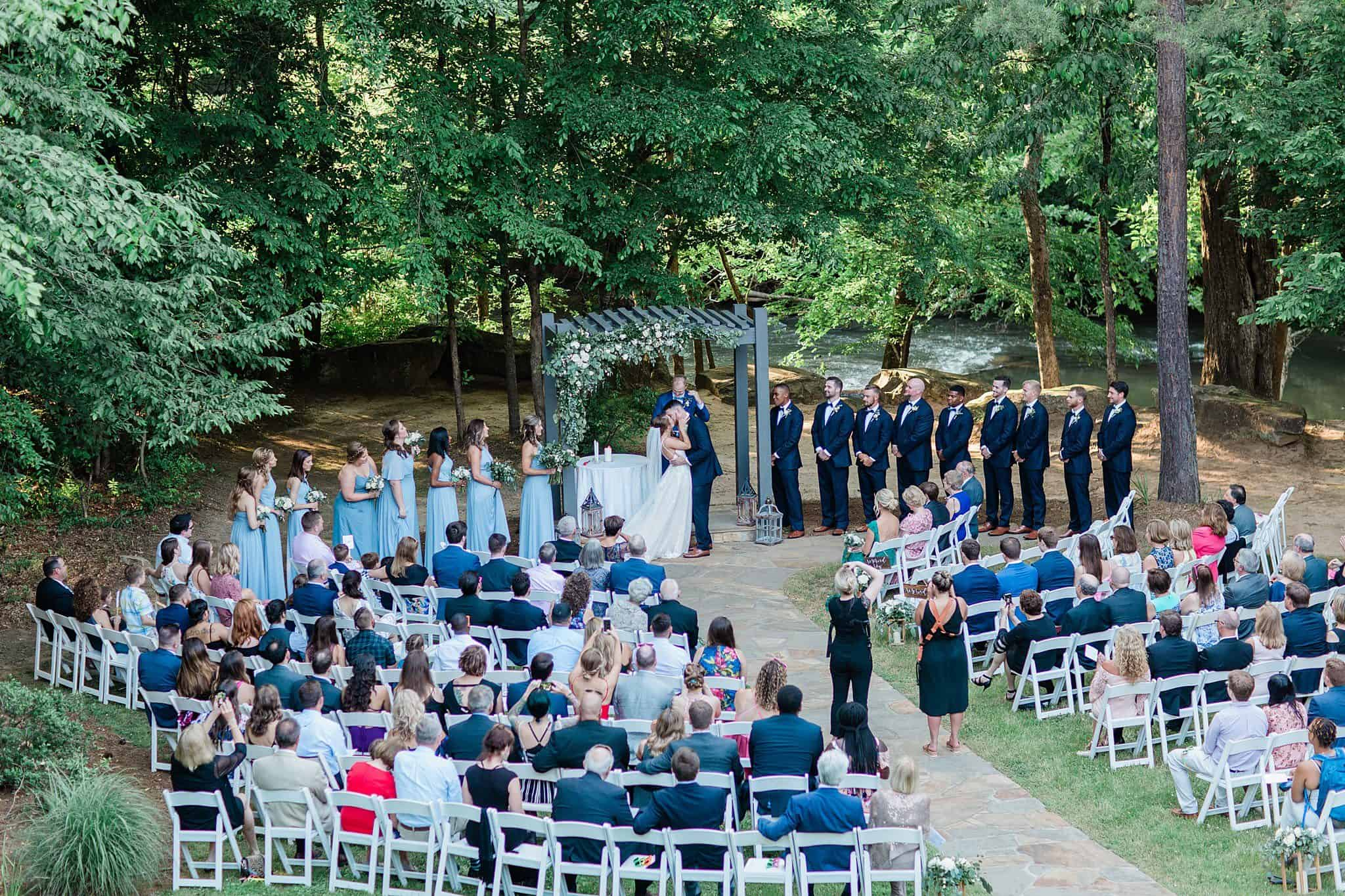 Bride and Groom kissing at altar at end of ceremony under arbor next to river