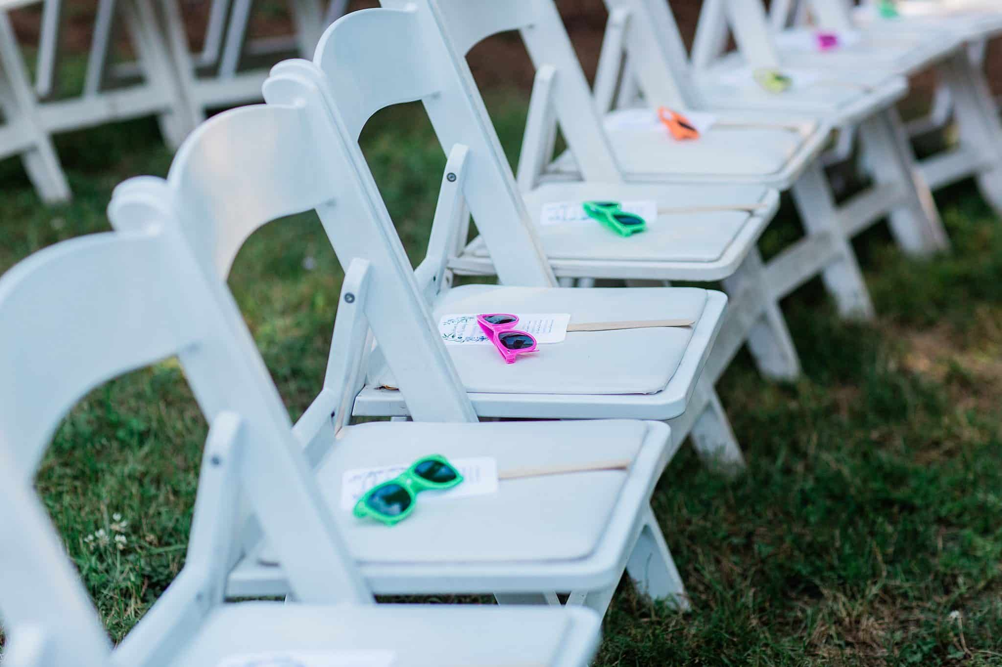 White Folding Chairs at Ceremony with sunglasses and fan for the heat outdoors