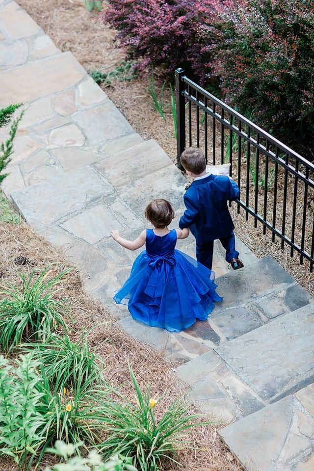 Flowergirl in blue dress holding the hand of the ringbearer holding the ringbearer pillow walking down steps to altar