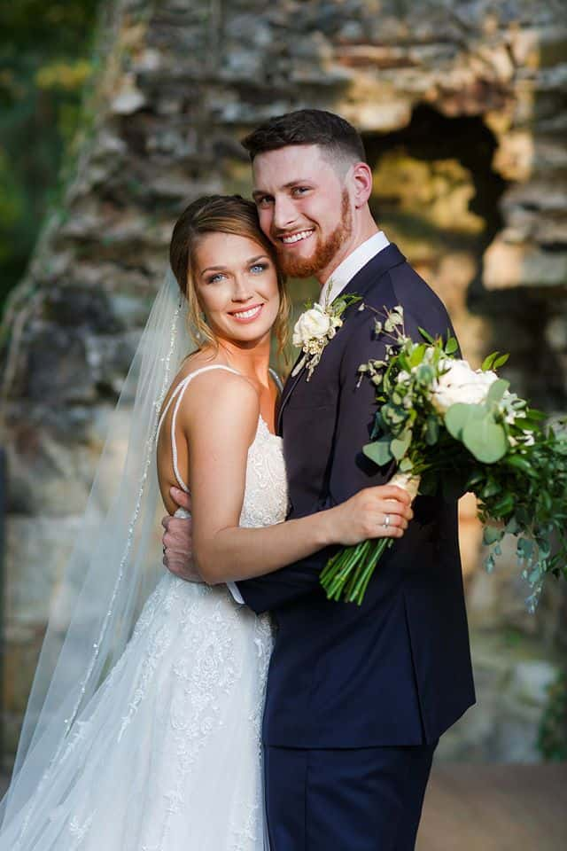 Bride and Groom posing outdoors in front of chimney