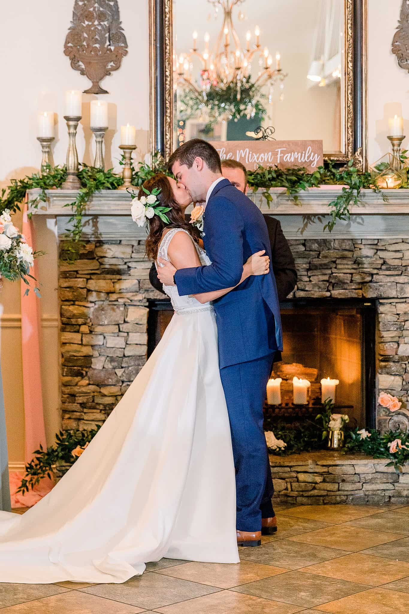 bride and groom kiss in front of fireplace