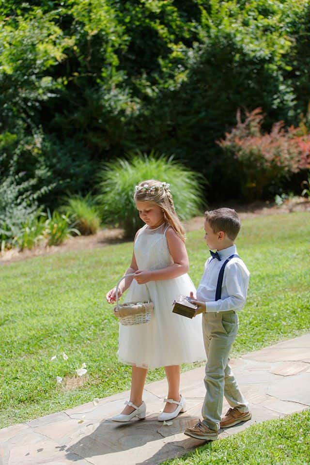 Flowergirl and Ring bearer walking together side by side as she drops rose petals during wedding ceremony processional