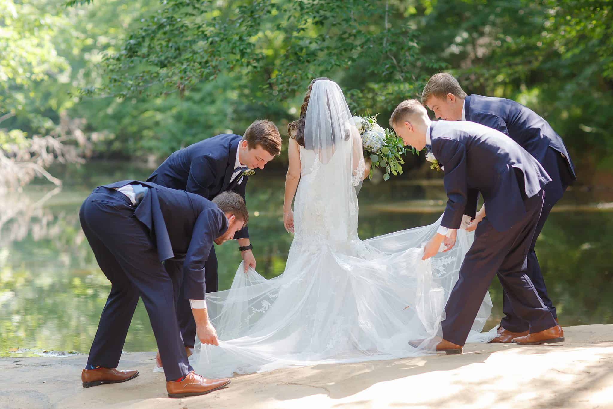 Bride with four groomsmen on the banks of the Yellow River holding her wedding gown's train