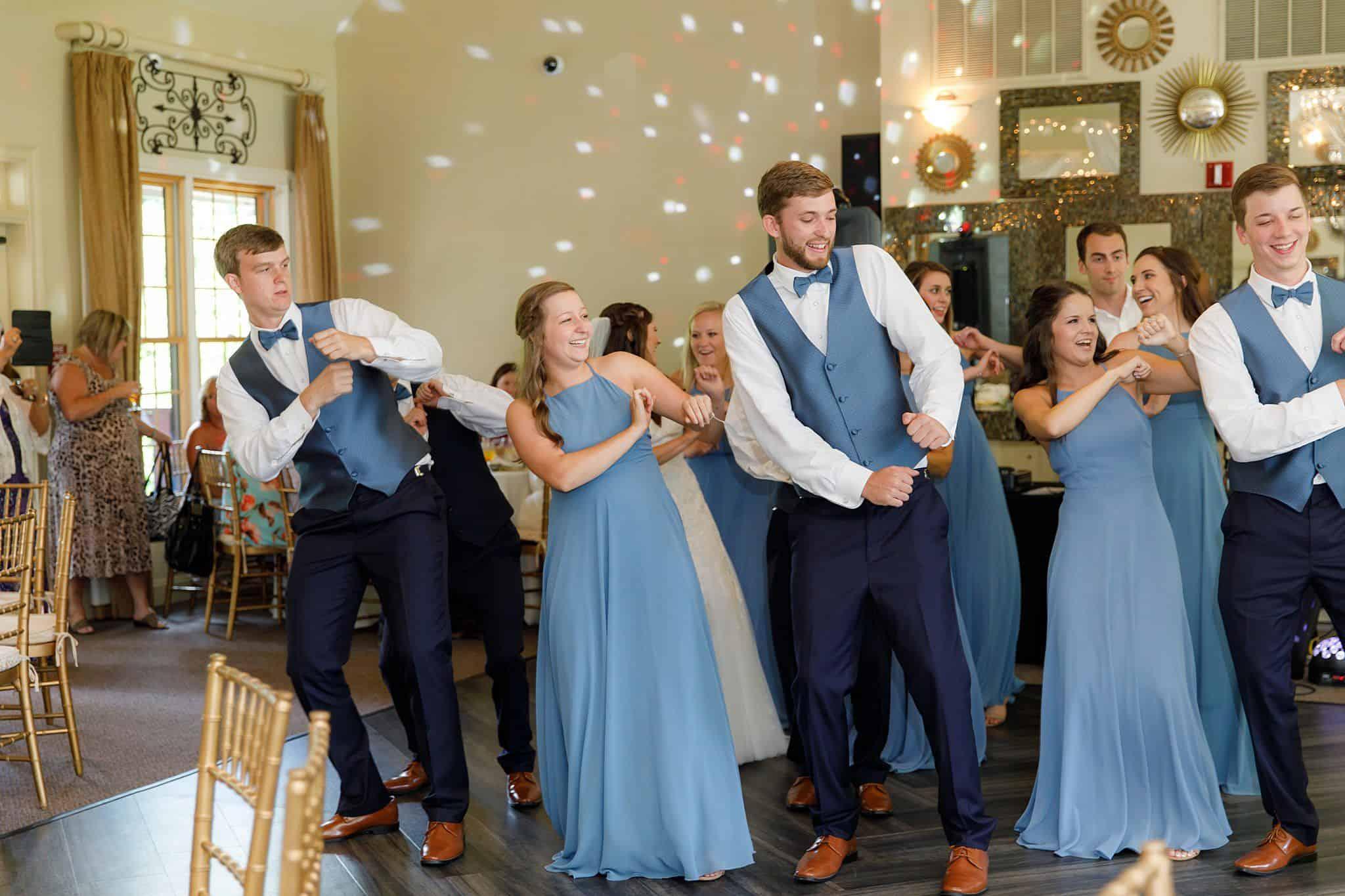 Bridesmaids and groomsmen dancing on dance floor at a wedding reception